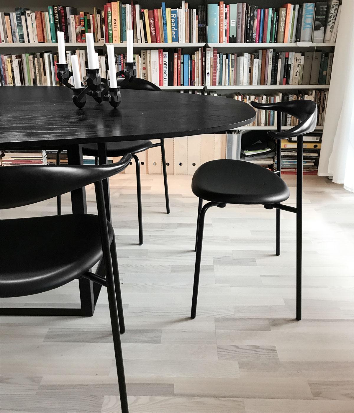 Den svarta läderklädda stolen CH88P med bordet Omni