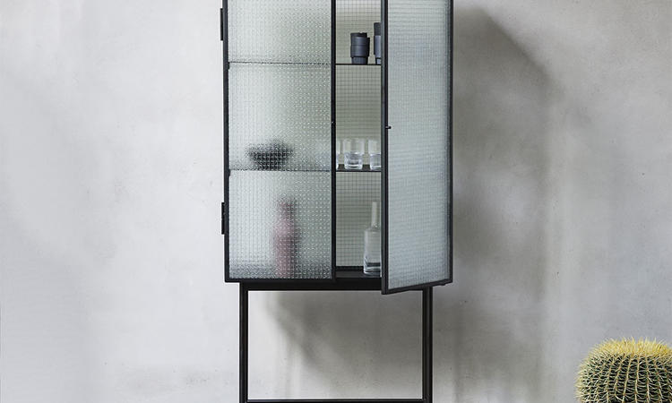 Haze från ferm LIVING är ett vitrinskåp med snygga dörrar i glas och stativ i stål
