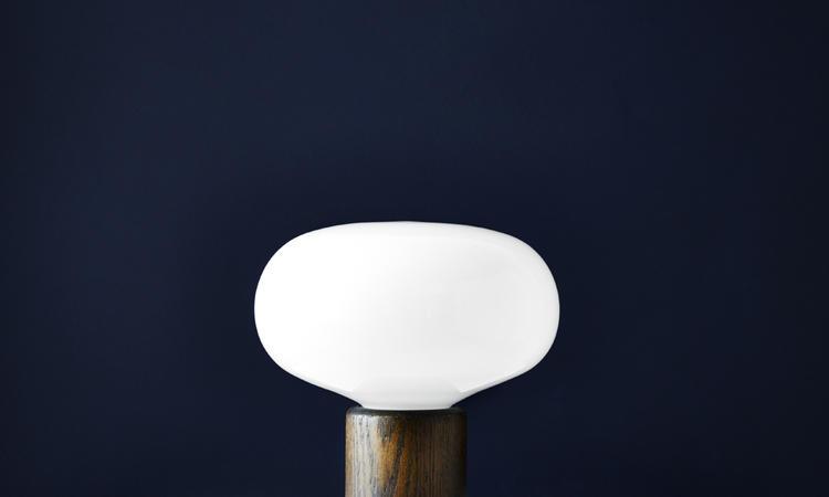 Olsson & Gerthel har lampan Karl-Johan i opalglas med bas i rökt ek
